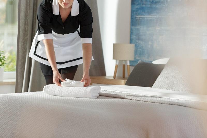 Camareira arrumando a cama