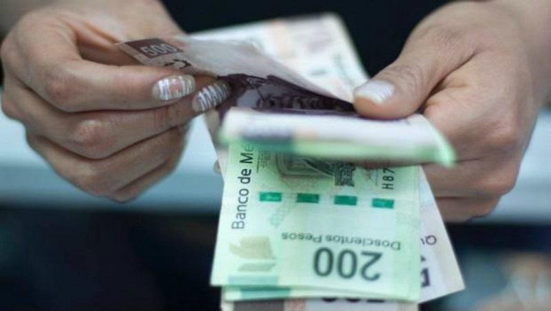 Pessoa contando pesos mexicanos em Cancún